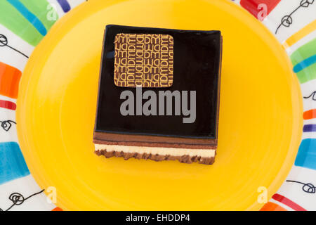 Marks & Spencer Triple Chocolate Layered Dessert on colourful yellow plate - Stock Photo