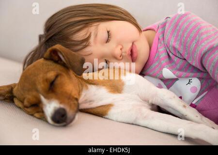 Toddler girl sleeping next to mixed breed puppy dog - Stock Photo