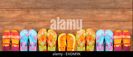 Brightly colored flip-flops on wood - Stock Photo