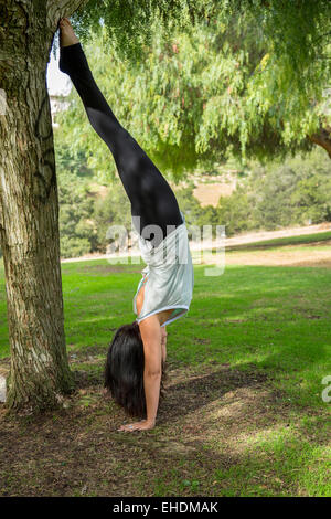 A woman performing a headstand in Balboa Park, San Diego, California - Stock Photo