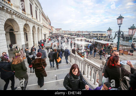 A large group of people walking on bridge next to Palazzo delle Prigioni on Riva degli Schiavoni in Venice, Italy. - Stock Photo