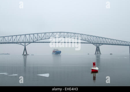 A Ship coming under the Francis Scott Key Bridge in Baltimore with ice in the harbor. - Stock Photo
