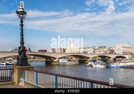 View of Waterloo Bridge spanning the River Thames and typical decorative lamppost on the South Bank walkway of the - Stock Photo