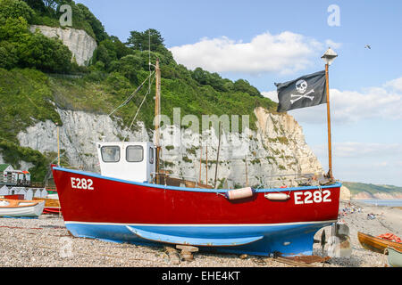Red fishing boat a flying Jolly Roger flag hauled up on the beach in Beer, east Devon, Jurassic Coast, south-west - Stock Photo