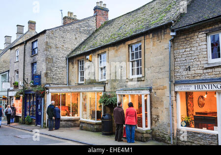 People window shopping in antiques shops, Stow on the Wold, Cotswolds, Gloucestershire in traditional Cotswold stone - Stock Photo