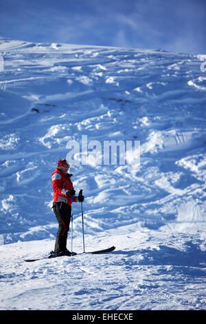 Wuman in red on ski slope - Stock Photo
