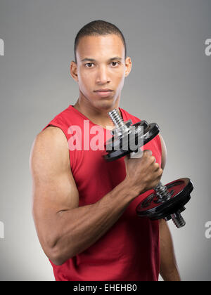 Muscular man wearing red tank top vest using barbell - Stock Photo