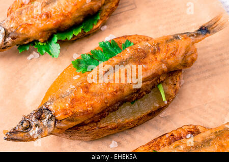 Fish and chips, fish in batter into slices of French fries on paper and newspaper - Stock Photo