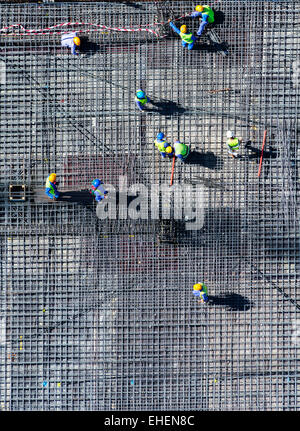 Migrant workers on construction site of apartment skyscraper tower in Dubai United Arab Emirates - Stock Photo