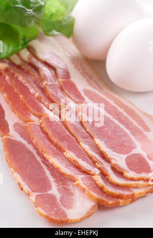 A plate with raw bacon eggs and lettuce. - Stock Photo