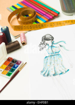 closeup of fashion designer workspace with sketches and designing equipment - Stock Photo