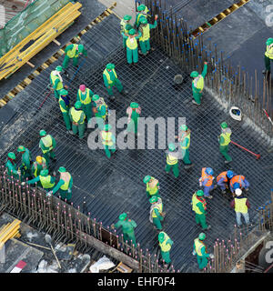 Migrant workers on construction site of high-rise  apartment skyscraper tower in Dubai United Arab Emirates - Stock Photo