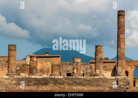 The columns of Jupiter temple in the forum of Pompeii, an old Roman city. Volcano Vesuvius in the background. - Stock Photo
