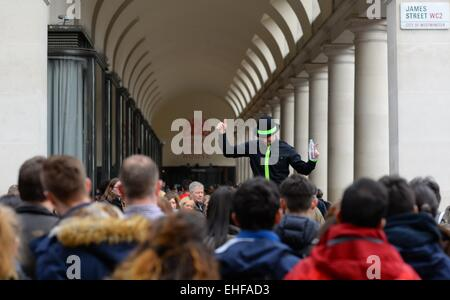 A Covent Garden street entertainer has the attention of a large crowd on James Street, London, UK. - Stock Photo