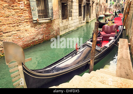 Small canal with parked gondola in Venice, Italy, waiting for tourists. Old medieval buildings and docked boats - Stock Photo