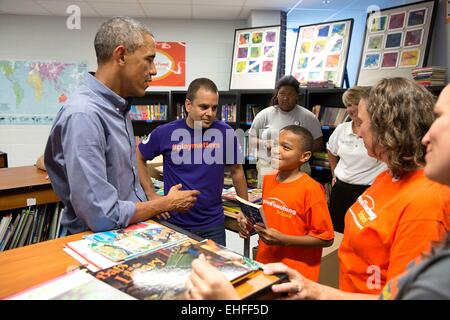 US President Barack Obama speaks with volunteers working in the school library during a National Day of Service and Remembrance project at the Inspired Teaching Demonstration Public Charter School September 11, 2014 in Washington, D.C.