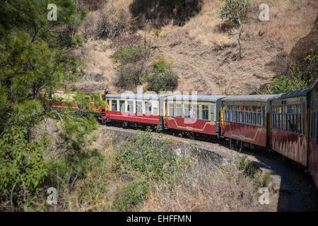 The narrow gauge Kalka-Shimla train winding down through the Himalayan foothills in India - Stock Photo