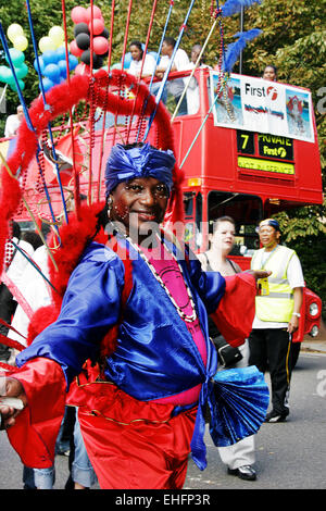 Mas dancer at Notting Hill Carnival with London bus behind. - Stock Photo