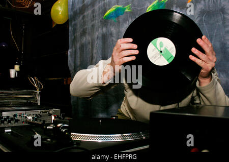 DJ hiding behind a record at a squat party in South East London. - Stock Photo