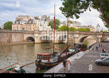 Paris, France - August 07, 2014: Tourists walking near by Pont Neuf. The oldest bridge across the Seine river in - Stock Photo