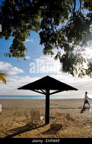 Guy walking down Jolly beach at sunset Antigua. - Stock Photo