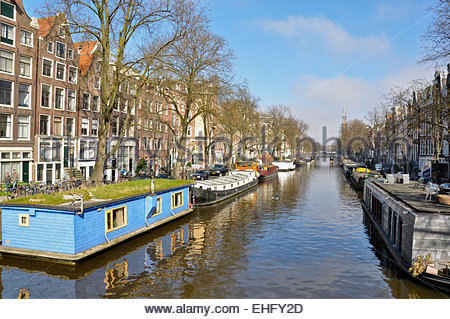 Houseboats line a canal in Amsterdam on a sunny day. - Stock Photo