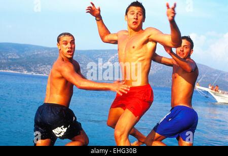 Three guys jumping into the sea in Ibiza. - Stock Photo