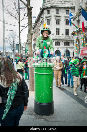 Tourist man dressed in green with leprechaun hat sits on green post box in O Connell Street, Dublin, Ireland, on - Stock Photo