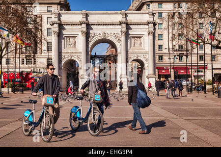 Marble Arch, London, England. Tourists walk  with hired cycles. - Stock Photo