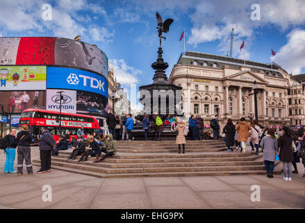 Piccadilly Circus, London, England, with the statue of Eros, crowds of tourists and a red London bus, on a sunny - Stock Photo