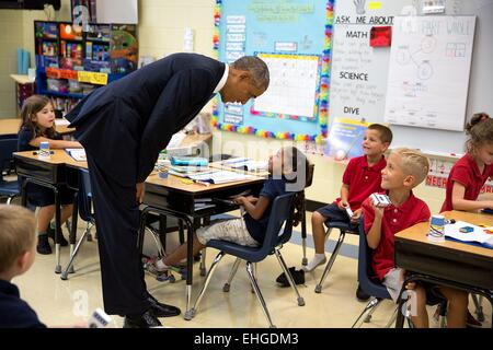 US President Barack Obama speaks with a young girl during a classroom visit at Clarence Tinker Elementary School - Stock Photo