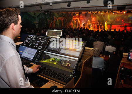 A lighting technician controls special effects for a live stage performance - Stock Photo