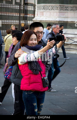 Tourists taking 'selfie' photo in front of Cathedral & Campanile, Piazza del Duomo, Florence, Tuscany, Italy - Stock Photo