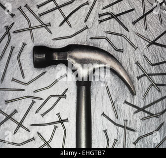 Hammer with bent nails on a silver slate background, scanned from a 5X4 transparency - Stock Photo