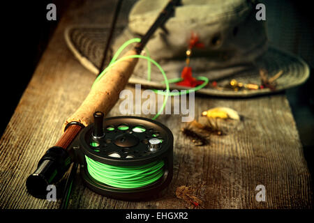 Fly fishing equipment with old hat on bench - Stock Photo