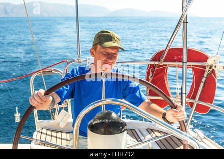 Young man skipper at the helm controls sailing yacht. - Stock Photo