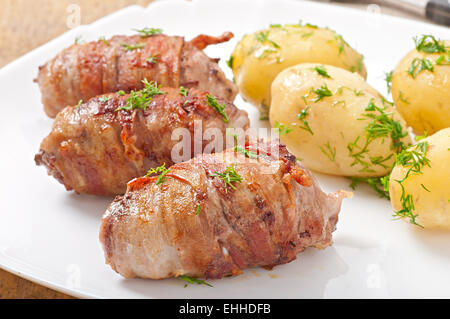 Grilled meat rolls wrapped in strips of bacon - Stock Photo