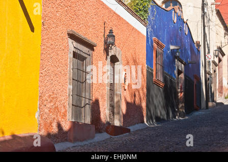Colorful Mexican houses on a steep cobblestone str - Stock Photo