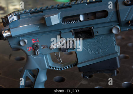 The grip and trigger of an assault rifle manufactured by Jesse James Firearms Unlimited of Dripping Springs, Texas, - Stock Photo