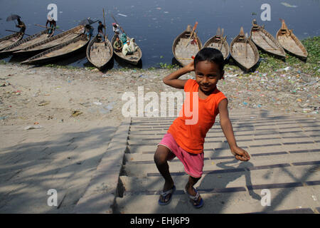 A child playing on the polluted Buriganga River bank in Dhaka, Bangladesh. Water pollution in the Buriganga River - Stock Photo