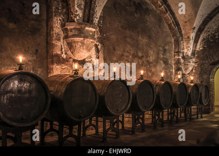 Old wine barrels in wine-cellar with candles - Stock Photo
