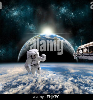 A team of astronauts work on a space station in orbit over a cloud covered world. A neighboring Earth-like planet - Stock Photo