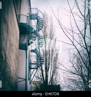 Berlin Spiral fire-escape staircase on side of building and treees - Stock Photo