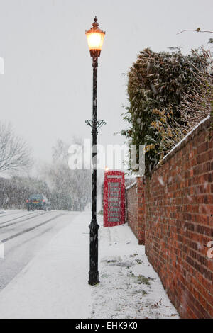 An old red telephone box and an old fashioned lamp post, on a village street covered in snow. - Stock Photo