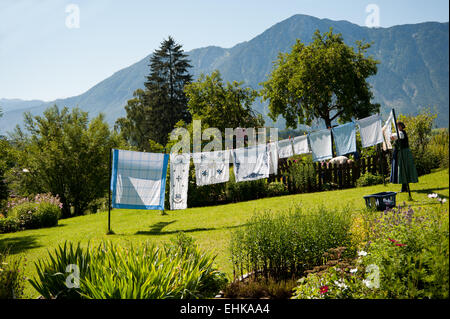 woman hanging out the laundry in her garden in Altaussee, Styria, Austria - Stock Photo