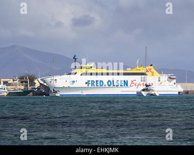 Catamaran car and passenger ferry, Fred Olsen Express busy in the canary islands, in the harbour of Corralejo  Fuerteventura - Stock Photo