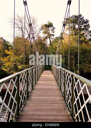 iron suspension bridge footbridge with wood slats over the River Wharfe,Ilkley - Stock Photo