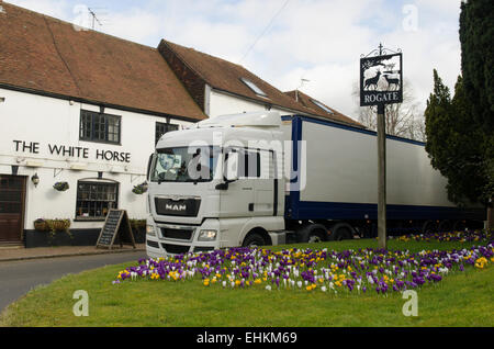 large lorry winding its way through narrow road around Rogate church on the A272 near Midhurst, Sussex, UK. Crocuses - Stock Photo