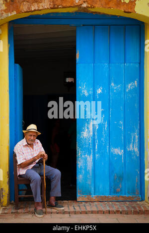 An old man sits in a doorway in Trinidad, Cuba - Stock Photo