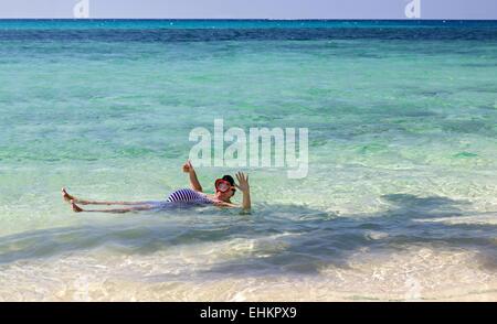 fat man in a retro swimsuit backstroke in the sea - Stock Photo